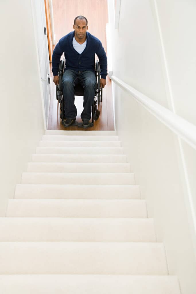 man in wheelchair at bottom of stairs who hates his body