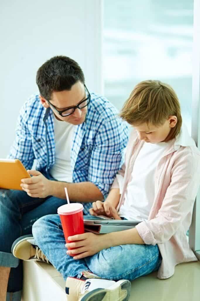 boy playing on device while dad helps him learn