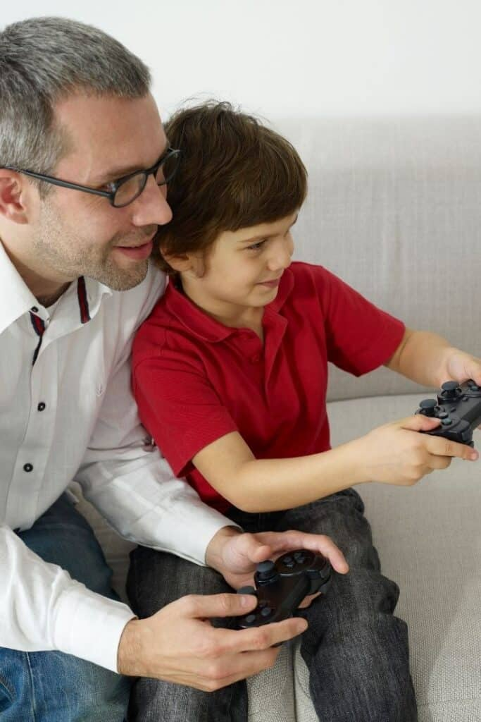 dad and boy playing video games together