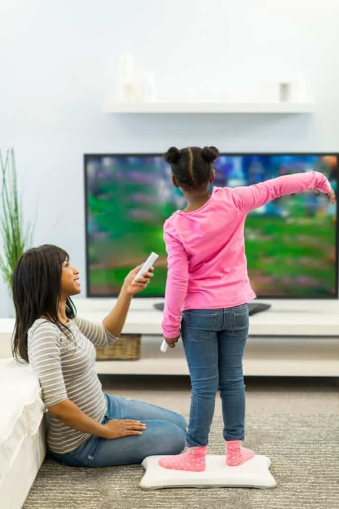 girl playing wii fit while mom waits her turn