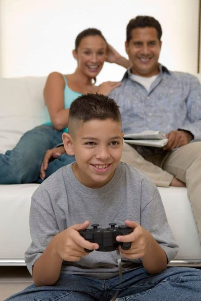 boy playing video game with parents looking on